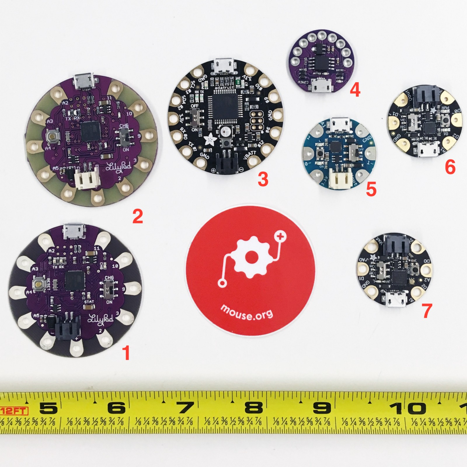 A picture of 7 different sewable microcontrollers and a Mouse sticker